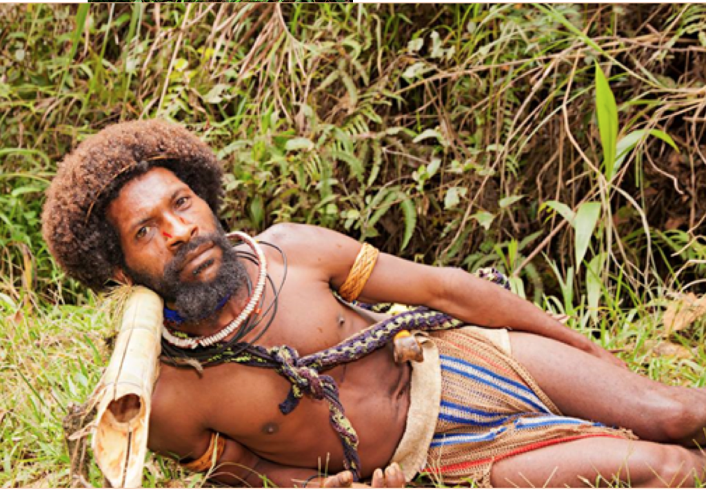 Huli wigmen sleeps on a pole at night so his hair is not disturbed